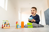 Small boy playing with little brick block toys at home on the floor smiling