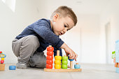 Small boy playing with little wood toys at home on the floor learning colors and counting