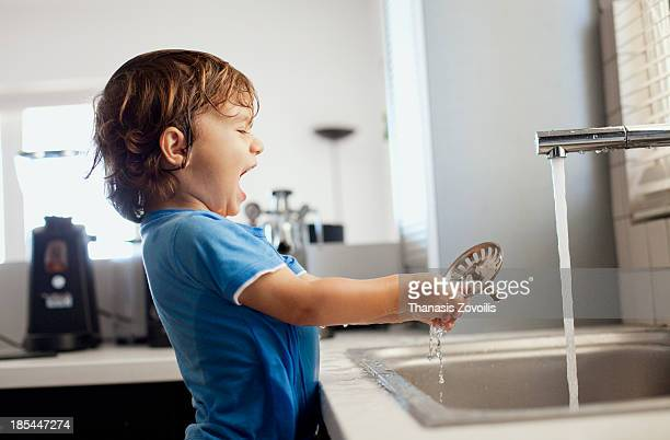 Small boy playing with water in the kitchen