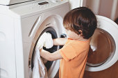 Small boy putting clothes in a washing machine