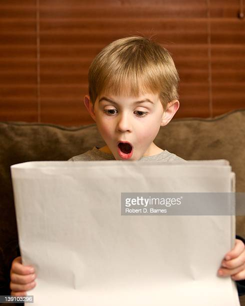 Small boy reading blank newspaper