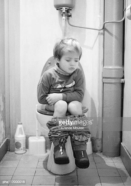 Small boy sitting on the toilet, b&w