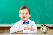 Small boy in shirt sitting with alarm clock near blackboard. Little student with books waiting for school lessons