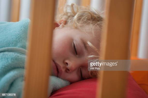 A small boy sleeps in his cot during his afternoon nap