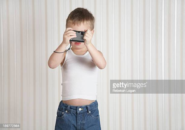 Small boy standing indoors holding camera.