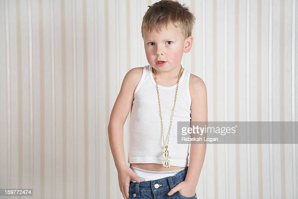 Small Boy standing indoors with hands in pocket.