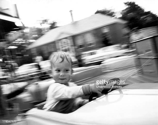 A small boy takes a turn at the wheel on a ride at The New York World's Fair New York New York 1964