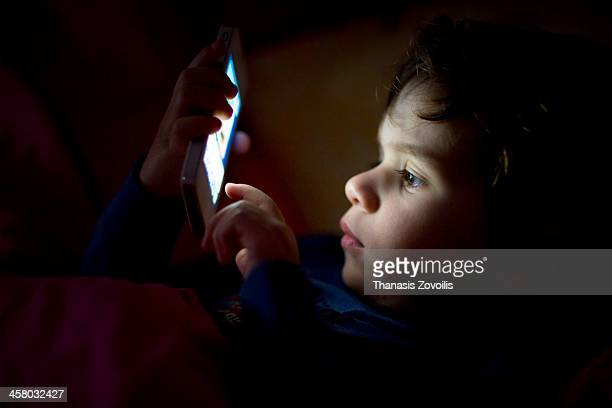 Small boy using a smartphone in the dark