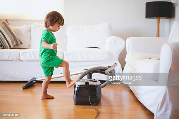 Small boy using a vacuum cleaner