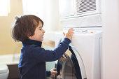 Small boy using a washing machine