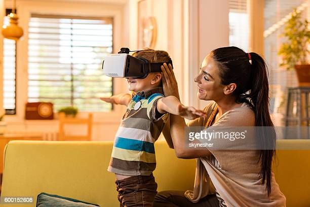 Small boy using virtual reality glasses with his mother.
