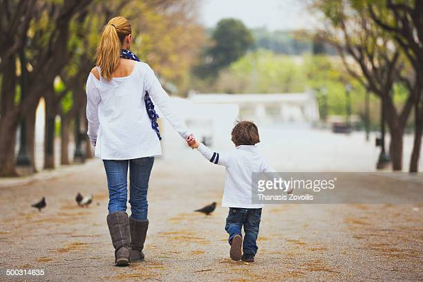 Small boy walk in a park with his mother