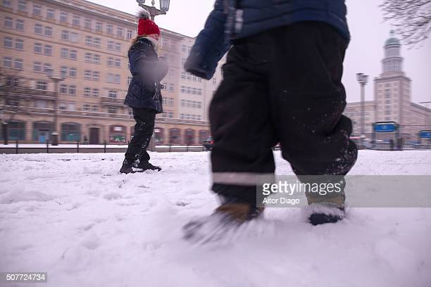 Small boy walking on the snow direct to the camera. Girl (13) with  closed eyes stays just behind him the bottom.