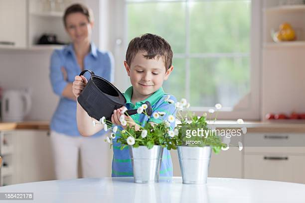 small boy watering plants