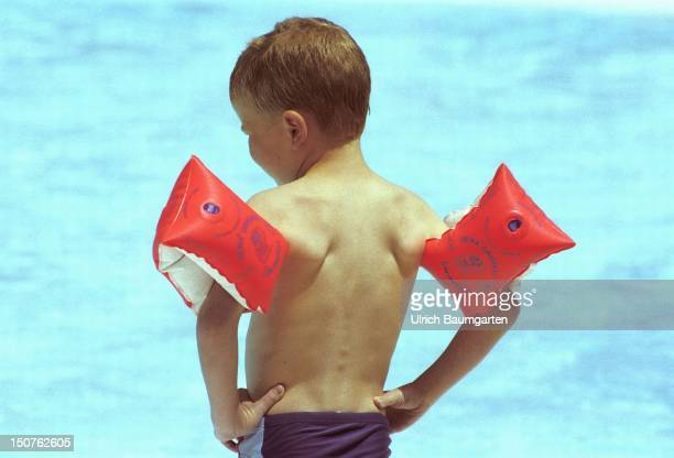 Small boy wearing swimming trunks and water wings stands in the sun at a swimming pool