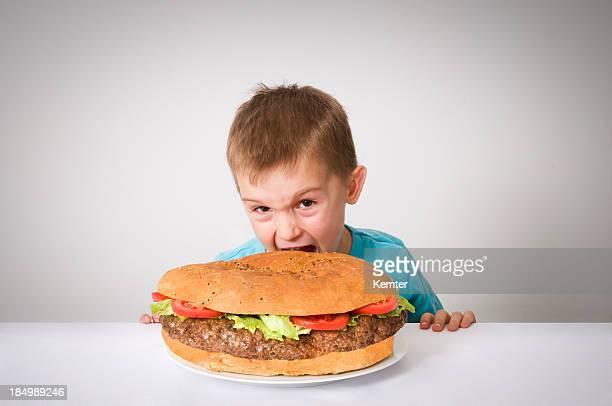 Pequeño niño con un enorme hamburguesa