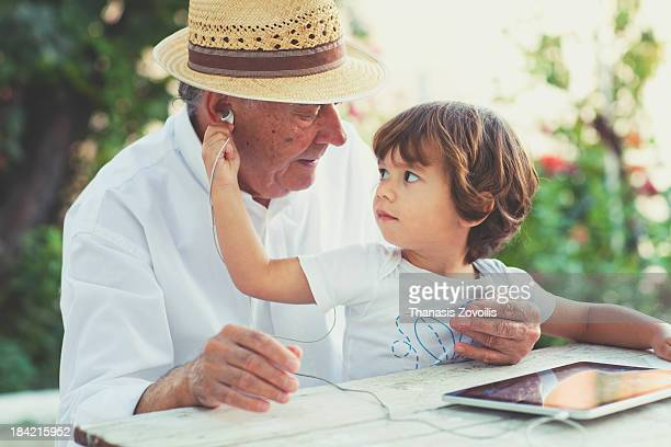 Small boy with his grandfather listening music