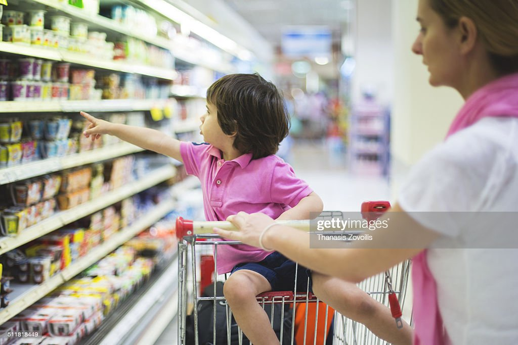 Small boy with his mother in a super market : Stock Photo