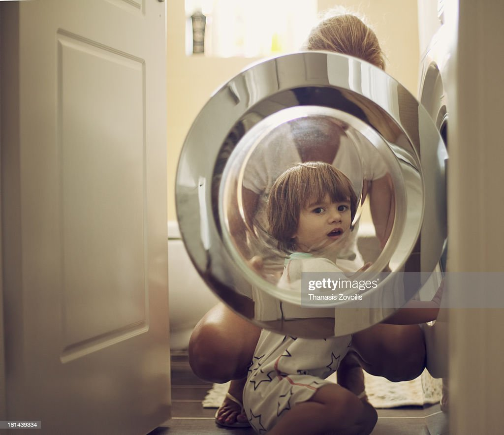 Small boy with his mother in front of a washing ma