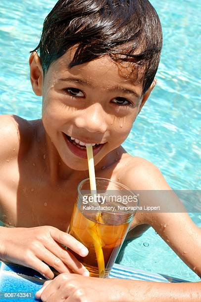 Small boy with iced tea in pool
