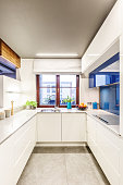 Vertical perspective on a small bright white kitchen interior with a window in the center, elegant countertops and blue modern glass elements