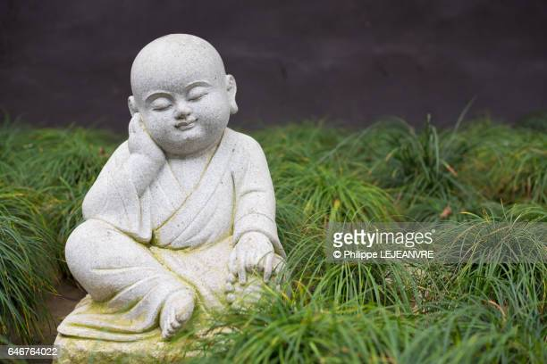 Small buddhist monk statue in a meditating pose on the grass