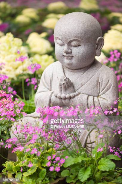 Small buddhist monk statue in a praying pose among flowers