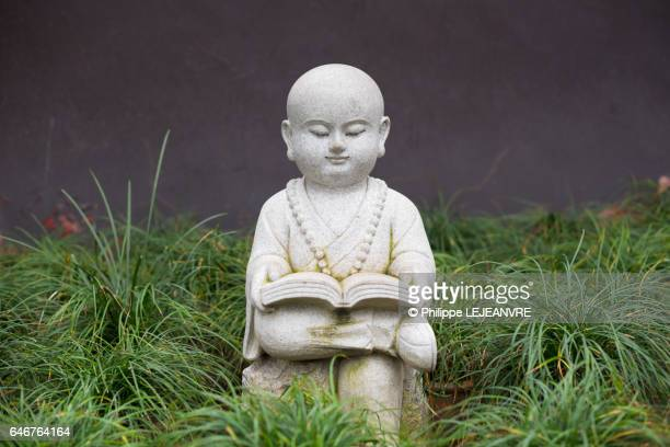 Small buddhist monk statue in a studying pose on the grass - center