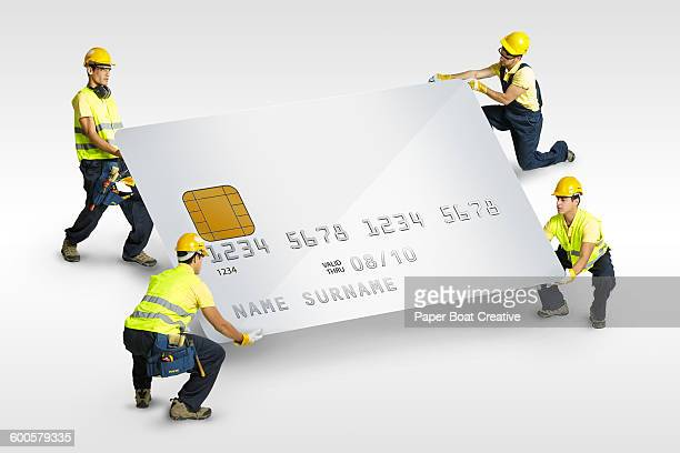 small builders carrying a giant credit card