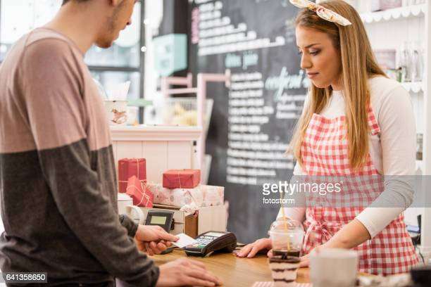 Small business owner accepting payment with contactless credit card reader