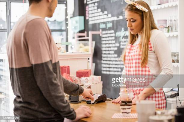 Small business owner accepting payment with slip credit card reader