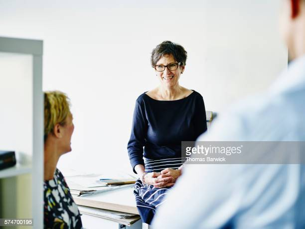 Small business owner in discussion with coworkers