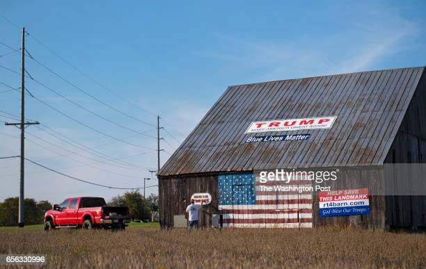 Small business owner Jason Scaggs age 36 touches up one of the many painted sentiments on his 'Flag Barn' in Owings MD on November 2 2016 The barn...