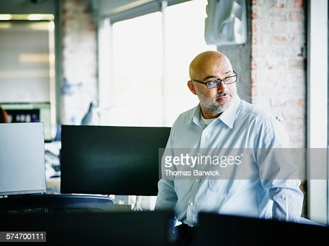 Small business owner looking out office window