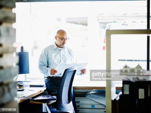 Small business owner looking over project plans