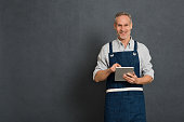 Smiling man using digital tablet for his business isolated on grey background. Portrait of happy mature man in blue apron isolated over gray wall. Satisfied business owner take orders on digital table