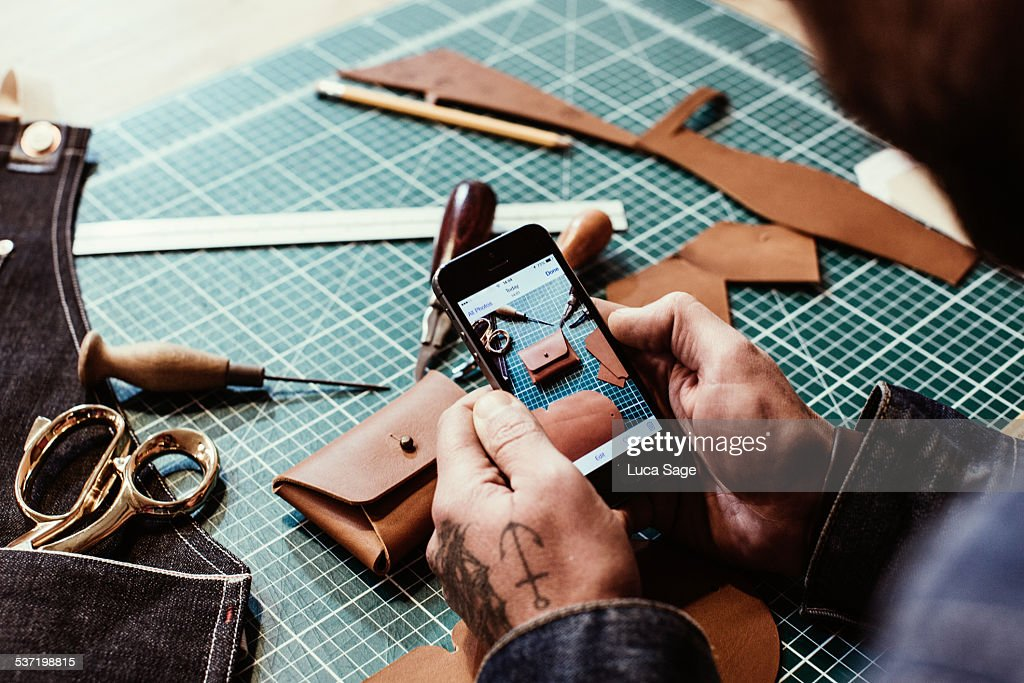 Small Business owner reviews photos of products : Stock Photo