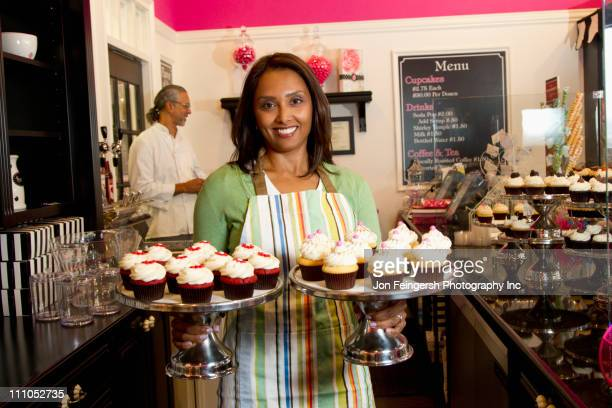 Small business owners with cupcakes in bakery shop