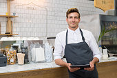 Successful small business owner holding digital tablet and looking at camera. Happy smiling waiter with apron and digital tablet leaning on counter. Portrait of young entrepreneur of coffee shop posin