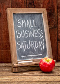 Small Business Saturday sign - white chalk handwriting on a blackboard agains rustic barn wood - holiday shopping concept
