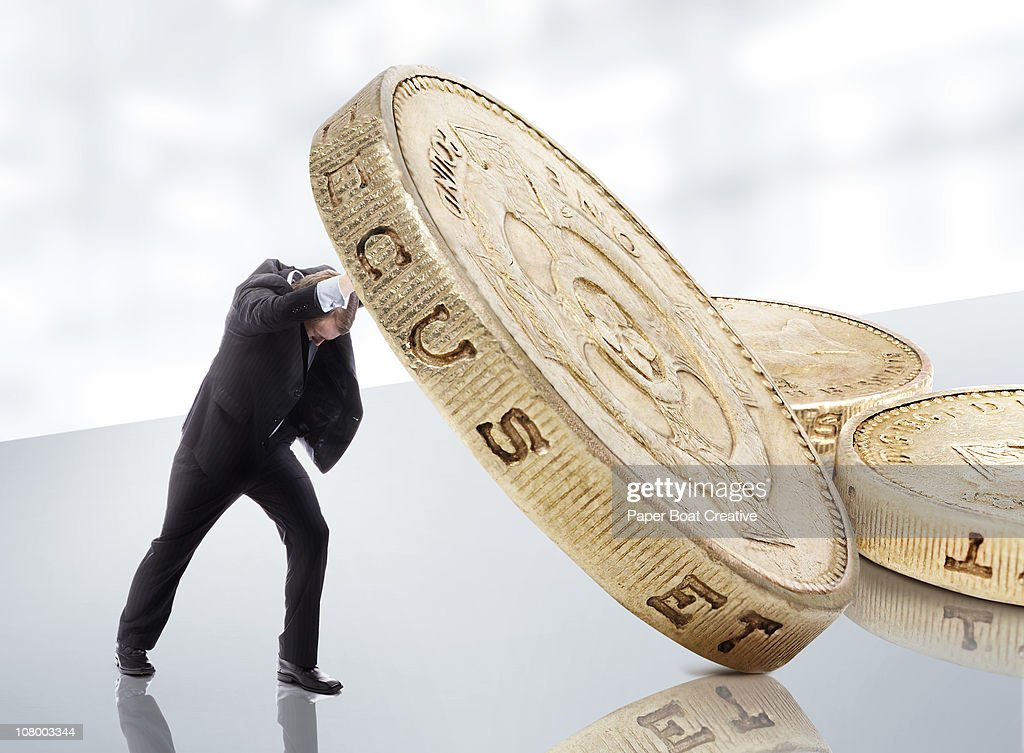 Small businessman lifting a gold pound coin : Stock Photo