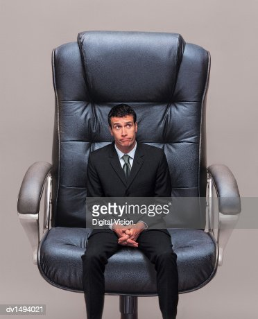 small businessman sitting in a big office chair stock photo