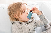 Small child using his inhaler device for asthma