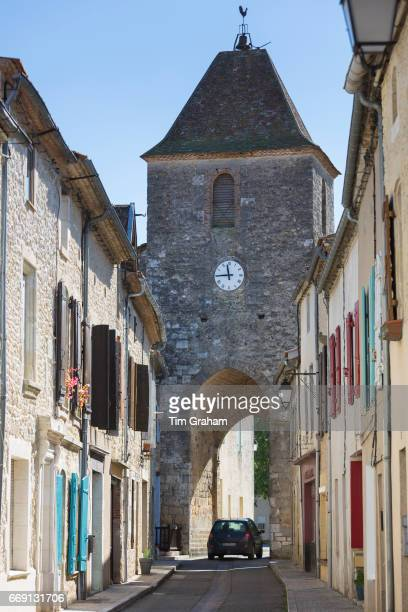 Small car passes through 13th Century medieval gateway clock tower in ancient bastide town Duras in Aquitaine France