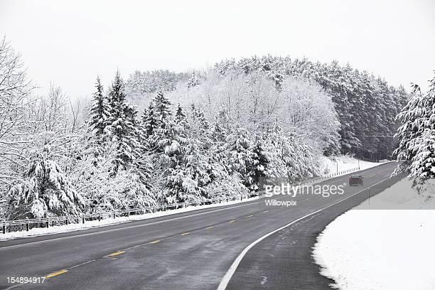 Small Car Speeding on Rural Adirondacks Highway in Blizzard