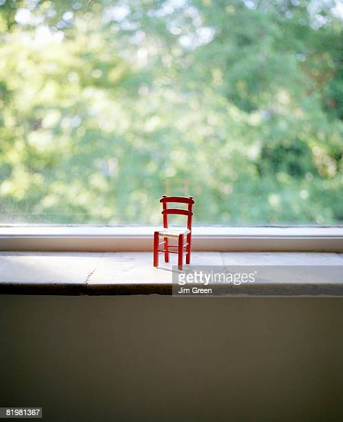 A small chair on a window sill