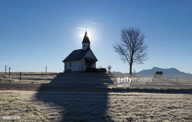 Small Chapel Schalchen close to Lake Chiemsee with horse grazing, Gstadt, Upper Bavaria, Germany