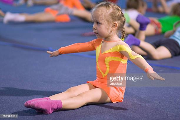 A small child gymnast following instructions