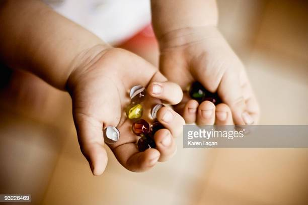 Small child holding marbles