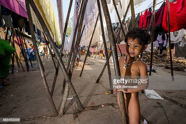 A small child is hiding behind wooden poles at Mahalaxmi Dhobi Ghat the world's largest outdoor laundry About 5000 workers live and work here doing...